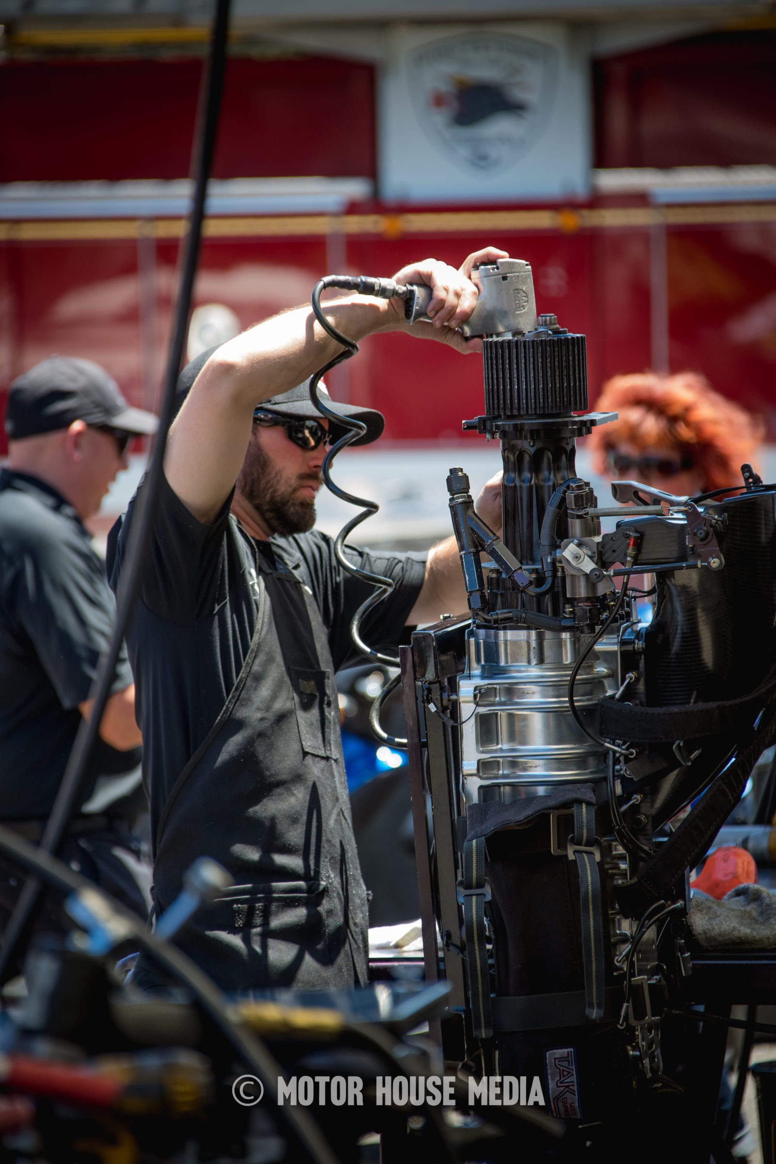 NHRA's Courtney Force's crew member taking apart supercharger